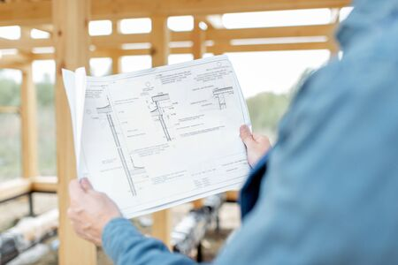Builder with blueprints on the construction site, building wooden frame house. Close-up on the drawings
