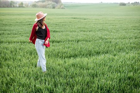 Stylish woman standing on the greenfield, enjoying springtime and nature. Concept of a carefree lifestyle on nature