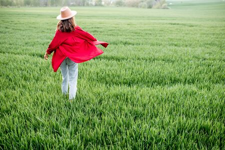 Stylish woman walking on the greenfield, enjoying springtime and nature, back view Concept of a carefree lifestyle on nature