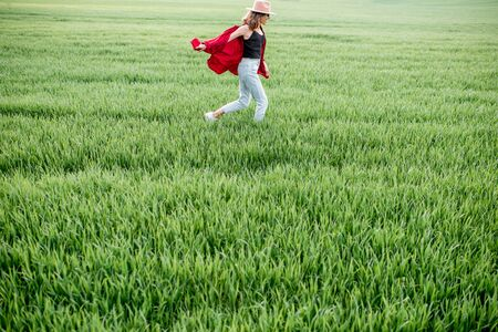 Carefree woman running on the greenfield, enjoying spring and nature, wide landscape view with copy space. Concept of a carefree lifestyle on nature