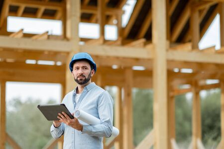 Portrait of an architect or builder with digital touchpad in front of the wooden house structure. Building and designing wooden frame house
