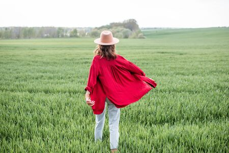 Stylish woman walking on the greenfield, enjoying springtime and nature, back view Concept of a carefree lifestyle on nature Stock fotó - 150297251