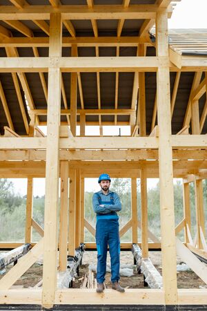 Builder in blue overalls and hard hat on the construction site, building wooden frame house