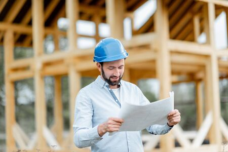 Builder or architect in hard hat supervising a project, standing with blueprints on the construction site. Building wooden frame house concept