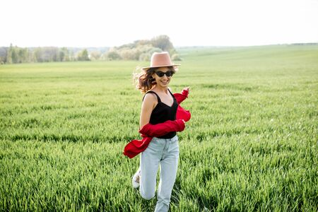 Portrait of a stylish carefree woman running on the greenfield enjoying nature in springtime. Concept of wellness and carefree lifestyle on nature 免版税图像