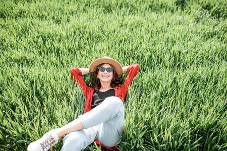 Portrait of a stylish carefree woman lying on the greenfield enjoying nature in springtime, view from above. Concept of wellness and carefree lifestyle on nature