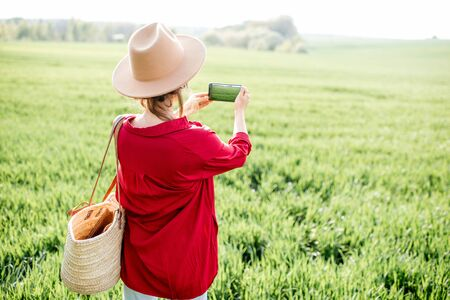 Woman photographing on phone while standing on the greenfield, enjoying springtime and nature, back view. Concept of a carefree lifestyle on nature Stock fotó - 150297493