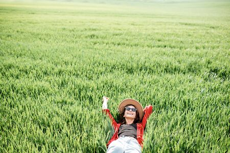 Portrait of a stylish carefree woman lying on the greenfield enjoying nature in springtime, view from above. Concept of wellness and carefree lifestyle on nature 免版税图像