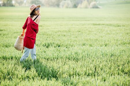 Portrait of a stylish carefree woman on the greenfield enjoying nature in springtime. Concept of wellness and carefree lifestyle on nature Stock fotó