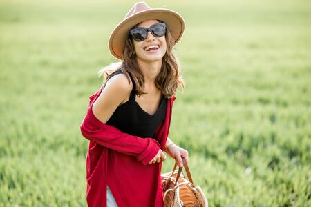 Portrait of a stylish joyful woman enjoying nature on the greenfield during a springtime. Concept of wellness and carefree lifestyle on nature 免版税图像