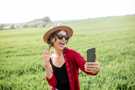 Young and joyful woman taking selfie portrait or talking on mobile phone while standing on the greenfield, enjoying nature in springtime 免版税图像