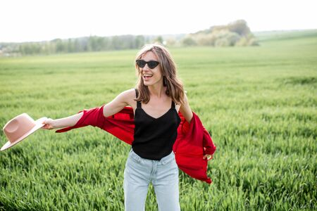 Portrait of a stylish carefree and active woman on the greenfield enjoying nature in springtime. Concept of wellness and carefree lifestyle on nature