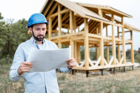 Architect or builder standing with blueprints near the wooden house structure on the construction site outdoors. Concept of building frame houses from wood 免版税图像