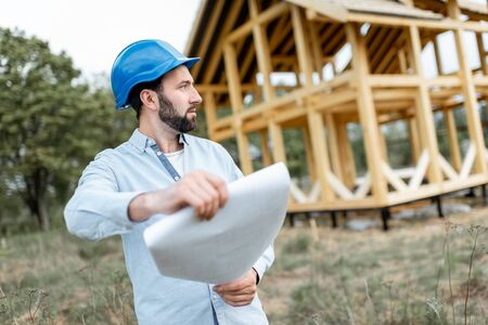 Architect or builder standing with blueprints near the wooden house structure on the construction site outdoors. Concept of building frame houses from wood