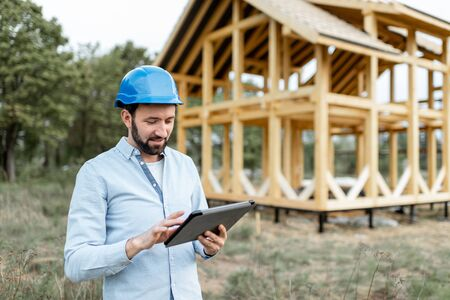Architect or builder with digital touchpad near the wooden house structure, building and designing wooden frame house 免版税图像