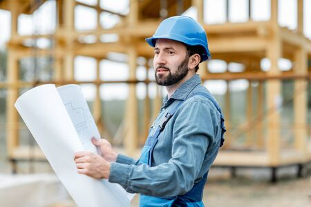 Portrait of a confident builder in blue overalls and hard hat standing with blueprints on the construction site. Building wooden frame house concept
