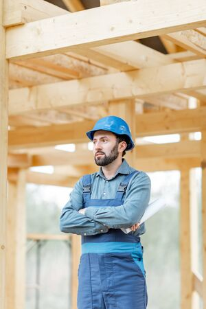 Portrait of a handsome and cofident builder in blue overalls and hard hat on the construction site. Building wooden frame house concept