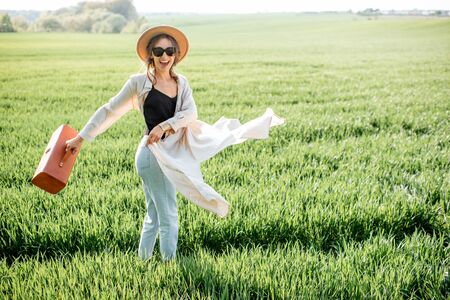 Portrait of a stylish woman walking with handbag on the greenfield, enjoying nature in springtime. Concept of wellness and carefree lifestyle on nature