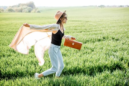 Portrait of a stylish and active woman running with handbag on the greenfield, enjoying nature in springtime. Concept of wellness and carefree lifestyle on nature