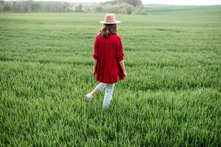 Stylish woman standing on the greenfield, enjoying springtime and nature, back view Concept of a carefree lifestyle on nature 免版税图像