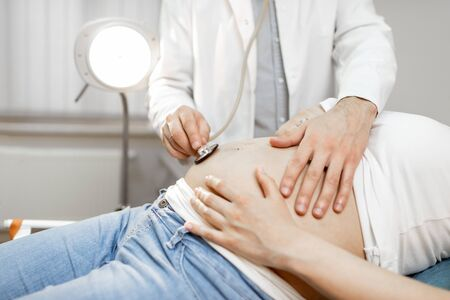 Doctor listening to a pregnant woman's belly with a stethoscope during a medical examination, close-up view