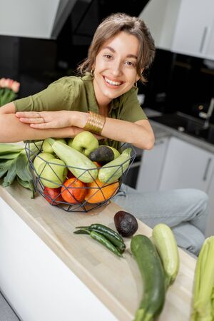 Portrait of a young and cheerful woman with healthy raw food on the kitchen at home. Vegetarianism, wellbeing and healthy lifestyle concept