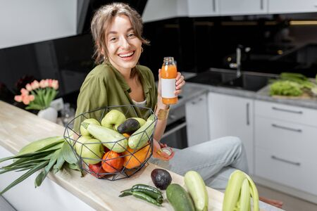 Portrait of a young and cheerful woman drinking juice, sitting with healthy raw food on the kitchen at home. Vegetarianism, wellbeing and healthy lifestyle concept 免版税图像