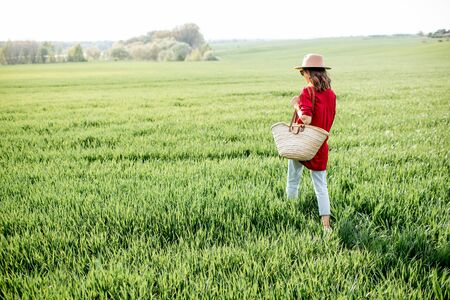 Stylish woman walking with bag on the greenfield, enjoying springtime and nature. Concept of a carefree lifestyle and beauty on nature