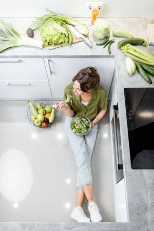 Woman eating healthy salad while sitting on the kitchen floor near the table full of fresh ingredients, view from above. Wellbeing and healthy eating concept Reklamní fotografie