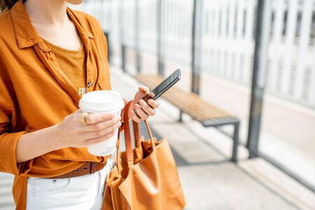 Business woman holding smart phone and coffee cup outdoors, close-up on hands, phone with black screen Reklamní fotografie