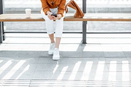 Woman sitting with phone at the public transport stop, cropped view with no face, focused on phone Reklamní fotografie