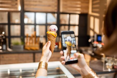 Young woman making a photo of yummy ice cream in waffle cone indoors. Buying ice cream at the shop