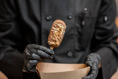 Chef in black uniform holding chocolate ice cream on a stick, close-up Reklamní fotografie