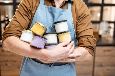 Salesman holding jars with variorus ice cream flavors at the shop Reklamní fotografie