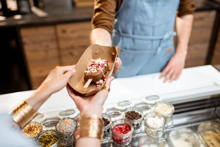 Buying or selling ice cream at the shop, close-up on chocolate ice cream