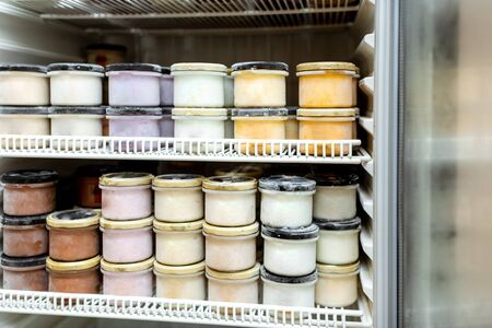 Fridge full of the ice cream packed in jars with a different flavors