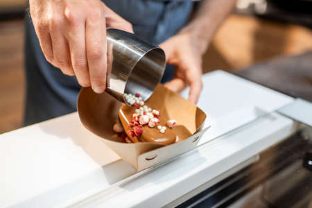 Seller making chocolate ice cream with toppings at the shop, close-up