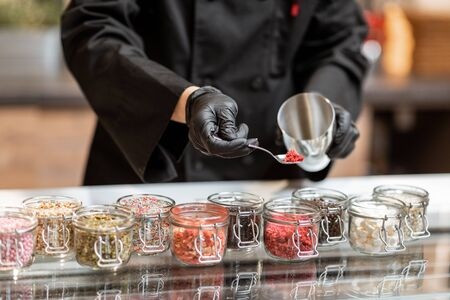 Chef mixing different ice cream toppings for sprinkling on the chocolate ice cream at the shop, close-up