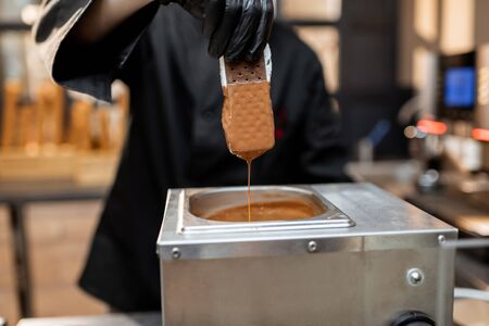 Chef in black workwear dips ice cream into the hot melted chocolate, making ice cream on a stick with toppings