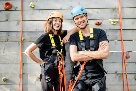 Portrait of an active well-equipped couple ready to climb the wall at the amusement park outdoors