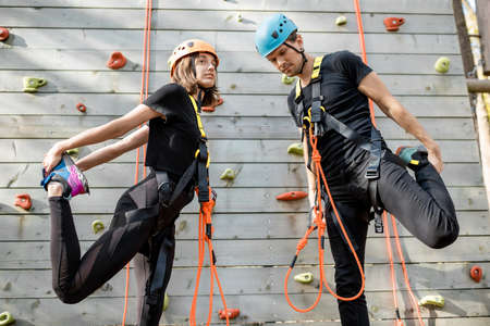 Young well-equipped sports couple warming up before climbing the wall in the park for sports entertainment