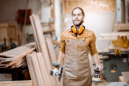 Portrait of a handsome carpenter in uniform with modern tools at the joinery workshop