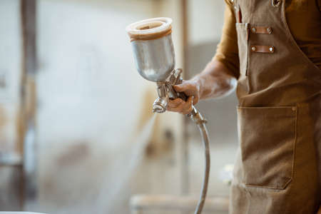 Painting wooden product with a spray gun at the painting shop of the carpentry, close-up