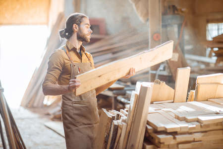 Carpenter or warehouse worker choosing raw wood material for the work at the sunny carpentry storage