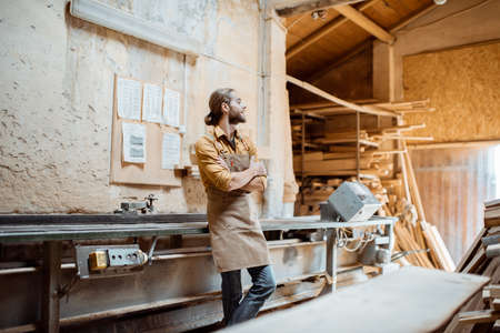 Portrait of a carpenter at the wood storage at the carpentry Stock Photo