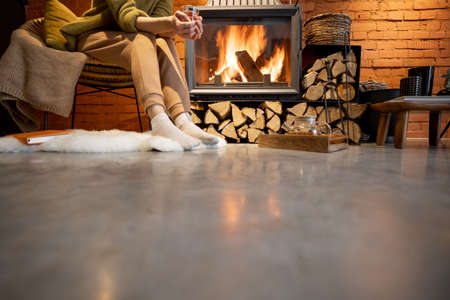 Young woman sitting with a drink by a burning fireplace, cropped image with no face. Cozy loft style interior
