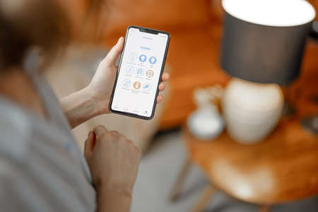 Smartphone with launch application for light bulb of floor lamp.