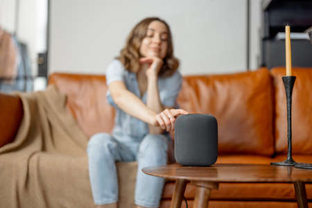 Woman touching black audio assistant column on the coffee table