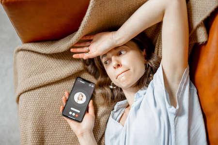 Woman feel bad lying on sofa and call a doctor 免版税图像