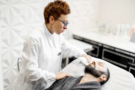 Man on ultrasound face lifting procedure in cosmetology salon